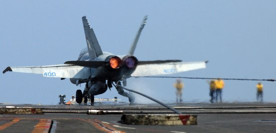 F-18 with afterburners lit as it catches an arresting cable