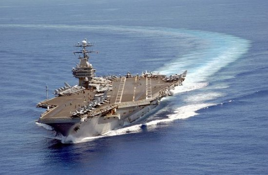 Aircraft carrier turning into the wind to begin air operations